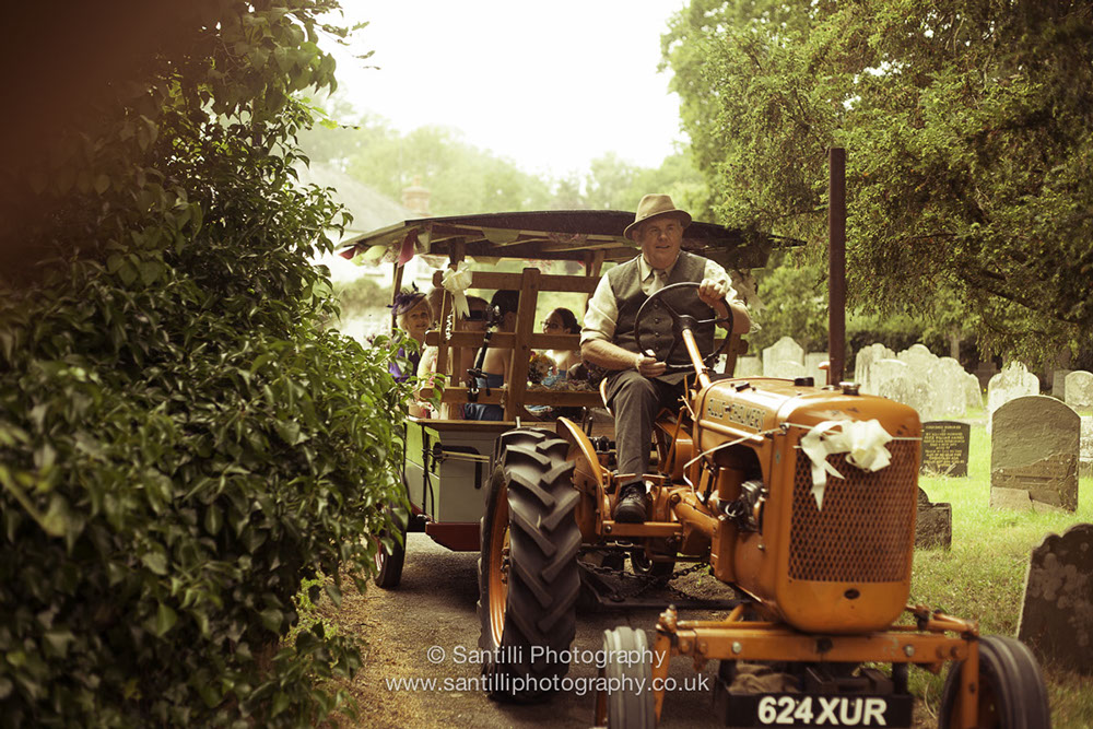 The bridal party is coming in her vintage tractor and beautifly decorated cart